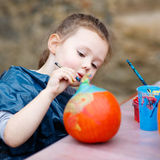 Little kid girl painting with colors on pumpkin Royalty Free Stock Photo