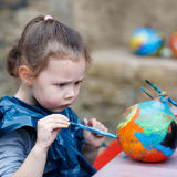 Little kid girl painting with colors on pumpkin. Happy little kid girl on a harvest festival, painting with colors a pumpkin. Child celebrating traditional royalty free stock photo