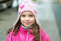 Little kid girl in ping jacket walking in the city. Smiling  chi Royalty Free Stock Photo