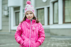 Little kid girl in ping jacket walking in the city. Smiling  chi Royalty Free Stock Photography