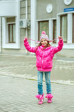 Little kid girl in ping jacket walking in the city. Smiling  chi Stock Images