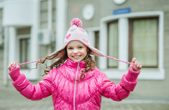 Little kid girl in ping jacket walking in the city. Smiling  chi Royalty Free Stock Images