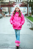 Little kid girl in ping jacket walking in the city. Smiling chi royalty free stock image