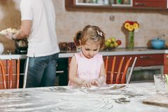 Little kid girl play with flour while daddy cooking in kitchen at table. Happy family dad, child daughter cooking food royalty free stock image