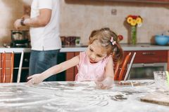 Little kid girl play with flour while daddy cooking in kitchen at table. Happy family dad, child daughter cooking food royalty free stock photography
