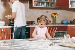 Little kid girl play with flour while daddy cooking in kitchen at table. Happy family dad, child daughter cooking food stock photos
