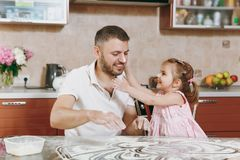Little kid girl play with man smearing dad with flour in kitchen at table. Happy family dad, child daughter cooking food royalty free stock photography