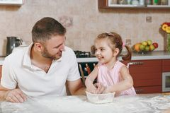 Little kid girl play, smearing with flour with man in kitchen at table. Happy family dad, child daughter cooking food stock image