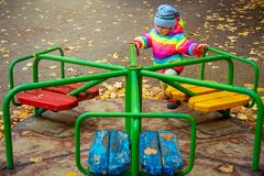 Little kid girl playing on carousel. child is riding carousel in children`s playground in autumn stock photos