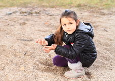 Little kid - girl playing in sand. Cute little kid - girl with ponytale clothed in black winter jacket and creme boots playing on sand Stock Photo