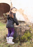 Little kid - girl playing with stump. Cute little kid - girl with ponytale clothed in black winter jacket and creme boots playing with stump Royalty Free Stock Photo
