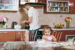 Little kid girl plays with flour while daddy cooking in kitchen at table. Happy family dad, child daughter cooking food stock photography