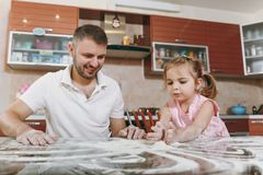 Little kid girl plays with man and draws on scattered flour in kitchen at table. Happy family dad, child daughter royalty free stock image