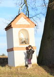 Little kid - girl praying by a chapel. Little kid - girl in winter clothes praying by a chapel in the meadows by the tree Royalty Free Stock Photography