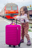 Little kid girl on railway station with suitcase with the train on background.  Royalty Free Stock Photos