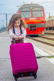 Little kid girl on railway station with suitcase with the train on background.  Stock Photo