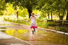 Little kid girl runs through a puddle. summer outdoor. Little kid girl runs through a puddle. outdoor royalty free stock photo