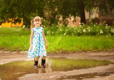 Little kid girl runs through a puddle. summer. Outdoor stock image