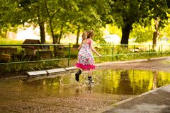 Little kid girl runs through a puddle. summer. Outdoor royalty free stock photos