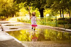 Little kid girl runs through a puddle. summer outdoor. Little kid girl runs through a puddle. outdoor royalty free stock photography