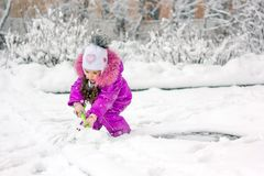 Little kid girl shoveling snow on home drive way. Little kid girl shoveling snow on home drive way Royalty Free Stock Photo