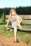 Little kid - girl sitting on a bench Royalty Free Stock Image