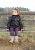 Little kid - girl sitting on a bench. Cute little kid - smiling girl clothed in black winter jacket and creme boots sitting on wooden bench Stock Image