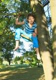 Little kid - girl sitting on branch Stock Image