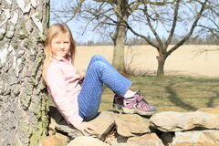 Little kid - girl sitting on stones Royalty Free Stock Images