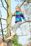 Little kid - girl sitting on tree Stock Images