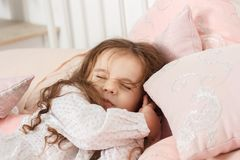 Little kid girl sleeping in a pink bed at home and watching dreams. Little kid girl sleeping in a pink bed at home and watching dreams Royalty Free Stock Photos