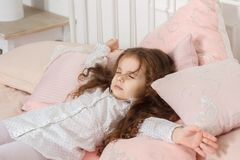 Little kid girl sleeping in a pink bed at home and watching dreams. Little kid girl sleeping in a pink bed at home and watching dreams Stock Photography