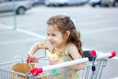 Little kid girl smiling while eating donut at shopping cart at mall parking. Royalty Free Stock Photography