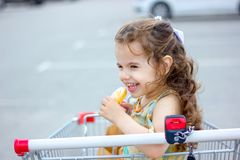 Little kid girl smiling while eating donut at shopping cart at mall parking. Royalty Free Stock Photos