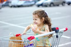 Little kid girl smiling while eating donut at shopping cart at mall parking. Royalty Free Stock Images
