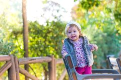 Little kid girl standing in a chair and smiling outdoors stock images