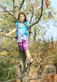 Little kid - girl standing on tree Royalty Free Stock Photos