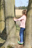 Little kid - girl standing on tree Royalty Free Stock Photo