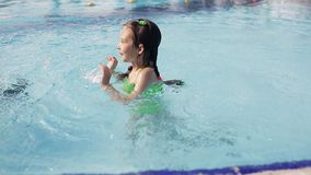 Little kid girl swim in a swimming pool clear water on summer resort stock video