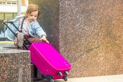 Little kid girl with travel suitcase outdoors. Stock Images