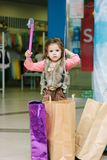 Little kid girl walking on a mall with shopping bag. Royalty Free Stock Photos