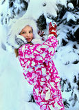 Little kid girl in winter clothes with falling Stock Image