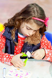 Little kid girl working at school doing workshop. Little kid girl working at school doing art work workshop cutting with scissors royalty free stock photography
