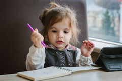 Little kid girl writing or drawing with pen in scetch book.  Royalty Free Stock Photos