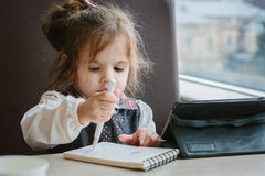 Little kid girl writing or drawing with pen in scetch book.  Stock Photo