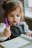 Little kid girl writing or drawing with pen in scetch book.  Stock Photos
