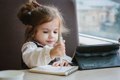 Little kid girl writing or drawing with pen in scetch book.  Royalty Free Stock Image