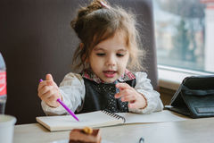 Little kid girl writing or drawing with pen in scetch book.  Stock Photography