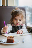 Little kid girl writing or drawing with pen in scetch book.  Stock Images