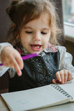 Little kid girl writing or drawing with pen in scetch book.  Stock Image